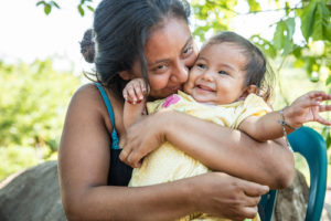 "SAN VICENTE, EL SALVADOR (12/3/15)-Fani Arevelo holds her 8 month old daughter Ivania, on the site of her family's new Habitat home, which was being built as part of Habitat for Humanity El Salvador's annual ""Christmas in Action"" build. © Habitat for Humanity International/Ezra Millstein"